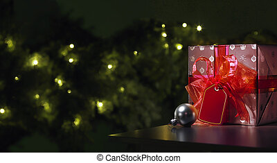 Red Christmas gift with a tree in the background