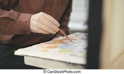 Artist painting with paintbrush. Close-up - Artist painting...