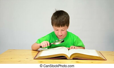 Little boy reading the book with magnifier