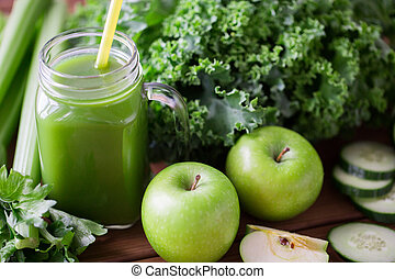 close up of jug with green juice and vegetables - healthy...