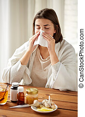 sick woman with medicine blowing nose to wipe