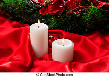 White candles on red satin background
