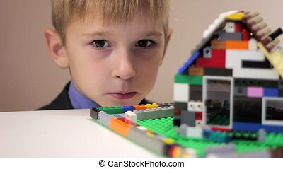 boy looks at a toy house