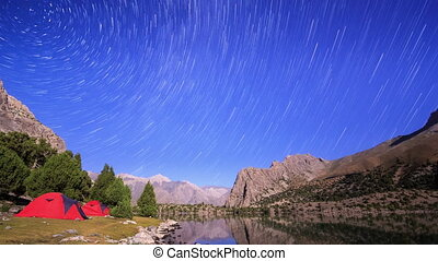 Moonlit night in the mountains. Traces of stars similar to...