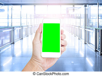 Hand holding blank green screen mobile phone