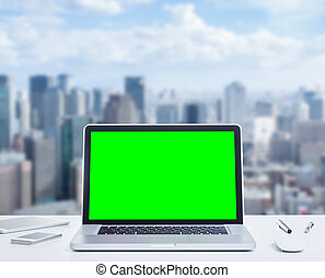 Blank green screen laptop computer on wooden table with...