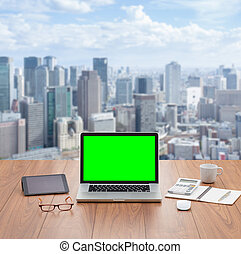 Blank green screen laptop computer with cityscape view on...