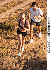 Athletic female runner and male fitness model running together