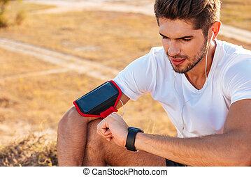 Concentrated young sportsman sitting and using smart watch...