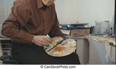 The old man artist painting. Looking into the camera