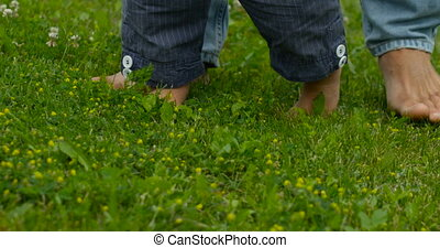 Legs of a young child and his father, a close-up on green grass at summer day