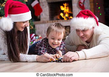 Kid boy playing toy cars with his parents under the christmas tree