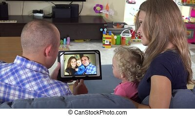 man woman and toddler girl watching family photos on tablet pc at home