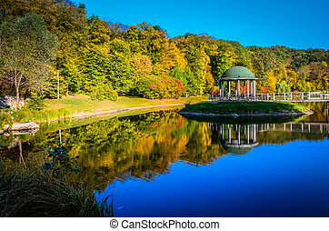 Gazebo in the park surrounded by fall foliage at autumn