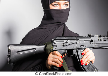 Muslim woman with a machine gun. An armed woman shoots....
