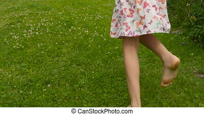 Camera following sweet girl in pink dress running away in the garden