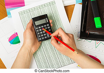 Calculator and pencil in female hands on background desktop.
