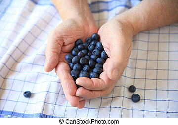 Fresh blueberries on male hands - A man holds blueberries in...