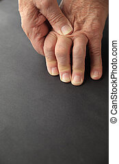 Senior with sore knuckles - Older man rubs his painful...
