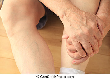 Man has both hands on his leg - Man sitting on floor with...