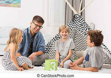 Male babysitter playing with children at home, tent in...
