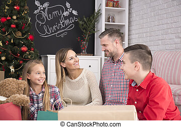 Family beside christmas tree - Happy family sitting in...