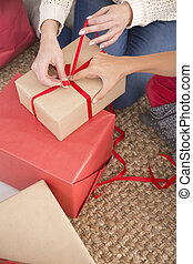 Woman tying red ribbon bow - Woman's hand tying red ribbon...