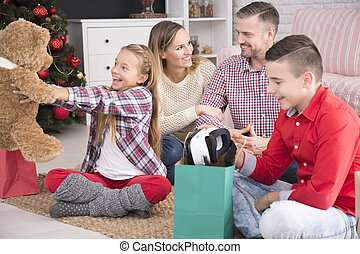 Children enjoying christmas gifts - Parents and they two...