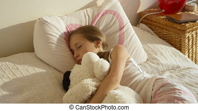 Adorable cute awaking girl in the bed with her toy