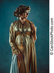 Pregnant woman in golden toga and wreath posing like a...