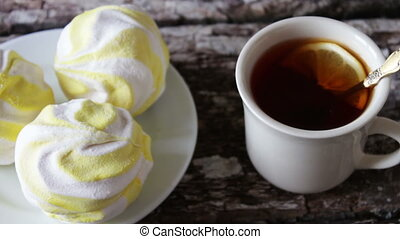 marshmallows and black tea with lemon - a delicious fresh...