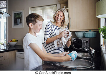 Mother and Son Doing the Dishes - Mother and son doing the...