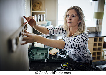 DIY in the Kitchen - Mature woman using a spirit level and...