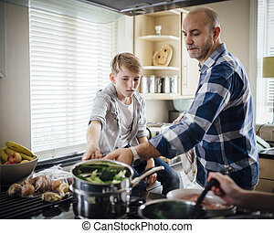 Helping Dad with the Cooking - Father and son cooking dinner...