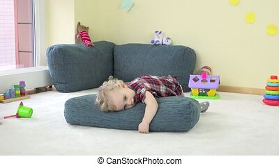 toddler child play with blue big pillow and show true...