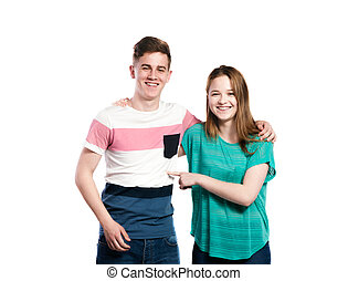 Teenage boy and girl, arms around each other, isolated. -...