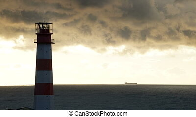 Timelapse lighthouse on the sea under stormy clouds and with the ship in the background