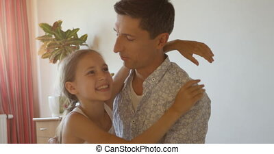 Charming portrait of happy father and daughter embracing at home interior background