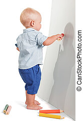 Little boy standing draws big red pencil isolated on white....