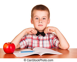 Cute boy sitting at table over exercise book, apple...