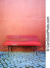 Minimalistic red bench and red wall .