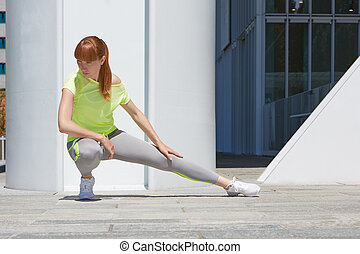 Woman stretching outdoor in the city, sunny day - Woman...