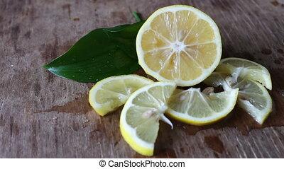 sliced lemon on a green background - Fresh ripe lemons on...