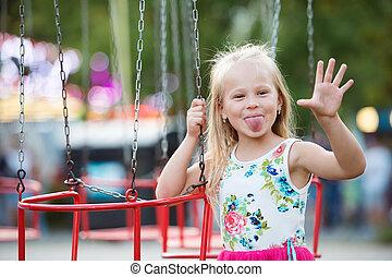 Cute little girl at fun fair, chain swing ride - Cute little...