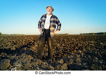 lifework - An elderly farmer standing in a plowed field....