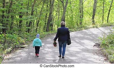 Grandmother and granddaughter walking city park