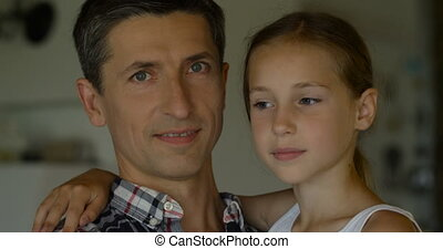 Close-up of cute girl embracing father at home, they smiling on the camera