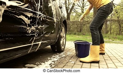 Girl washing automobile in open air. Handheld shot. Grading...