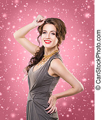 Young brunette woman in a dress on a snowy background -...