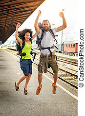 Two happy tourists jumping at the railway station